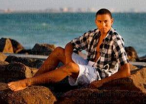 Young male model photographed in Dunedin, FL on rocks.